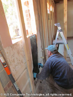 The homeowner wraps his wall with StrongHold's carbon fiber fabric.